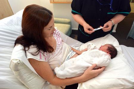 body temperature: AUCKLAND - JUNE 10 2014: A Midwife checking newborn temperature.A healthy persons average  body temperature is 98.6°F (37°C)