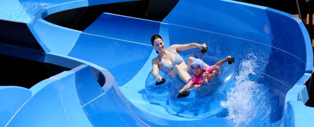aqua park: Young mother and child (girl age 04)  having fun in water park. Concept photo with copy space