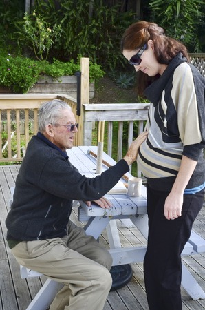30 years old woman: Grandfather (95 years old) holds his pregnant granddaughter (30) abdomen. Concept photo of pregnancy, pregnant woman family lifestyle.