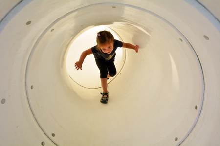 kids games: Child (girl age 05) plays in playground tunnel. Concept photo childhood. copy space