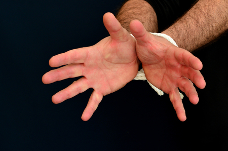 kidnapped: Hands of a missing kidnapped, abused, hostage, victim man  tied up with rope in emotional stress and pain, afraid, restricted, trapped, call for help, struggle, terrified, locked in a cage cell. Stock Photo