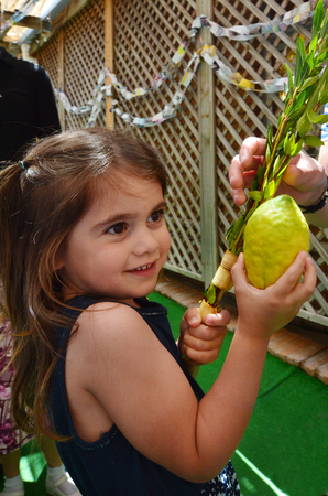 sukkoth festival: Jewish girl blessing on the four spices in a Sukkah on Sukkot Jewish Holiday.