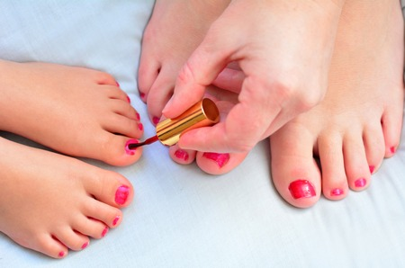 beautiful feet: Young mother (30) and her girl child daughter (4 years old) paint their feet with nail polish together. Stock Photo