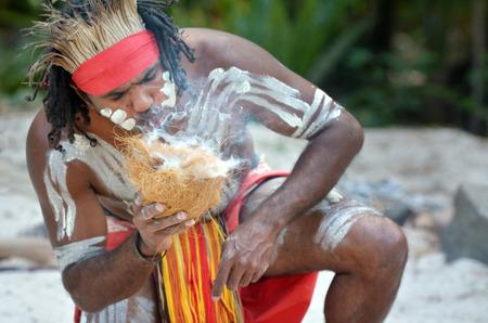 Portrait of one Yugambeh Aboriginal warrior demonstrate  fire making craft during Aboriginal culture show in Queensland, Australia.