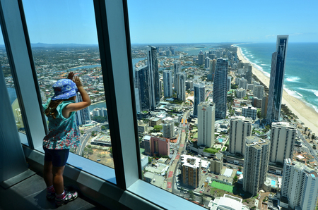 australia: Child (girl age 04) looks at the view of Surfers Paradise from the Skypoint observation deck at the top of the Q1 on the Gold Coast, Australia.