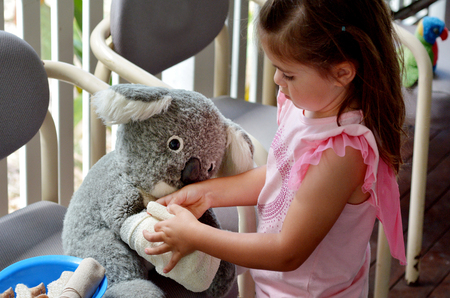 pretend: Little girl play pretend to be animal doctor (Veterinary physician), placing a bandage over an arm of injured Koala soft toy doll.