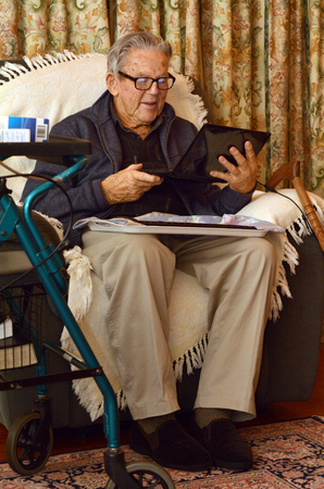 geriatrics: Old man (90s) in eyeglasses working with laptop computer at home. Lifestyle concept technology, oldness, old age, retirement, family.