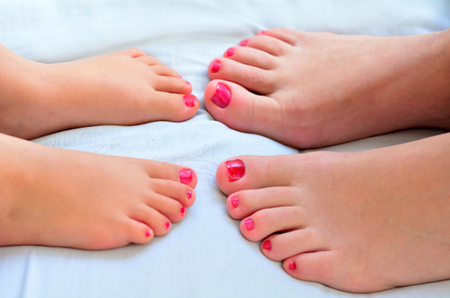 Young mother (30) and her girl child daughter (4 years old) compare the size of their painted nail polish feet. Stock Photo