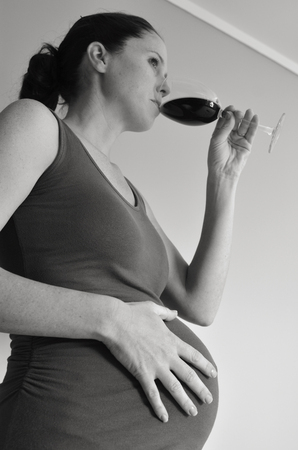 alcohol drinks: Pregnant woman drinks alcohol (red wine) during pregnancy .Concept photo of pregnancy, pregnant woman lifestyle and health care. copyspace (BW) Stock Photo