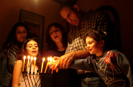 A family is lighting a candle for the Jewish holiday of Hanukkah. Banque d'images