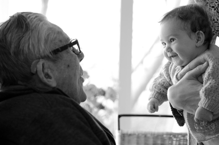 home visit: Great Granddad play with his great grandchild during home visit. Concept photo of senior citizen, retirement, pensioner, relationship, health and aging. Stock Photo