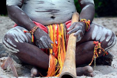 australian ethnicity: Yugambeh Aboriginal body coverd with body paint holds didgeridoo during Aboriginal culture show in Queensland, Australia. Stock Photo