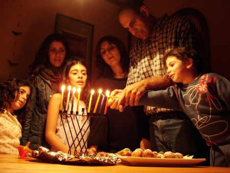 A family is lighting a candle for the Jewish holiday of Hanukkah. Stock Photo