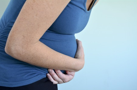 stressed woman: Pregnant woman with stomachache holds her tummy in pain. Concept photo of pregnancy, pregnant woman lifestyle and health care.copyspace Stock Photo