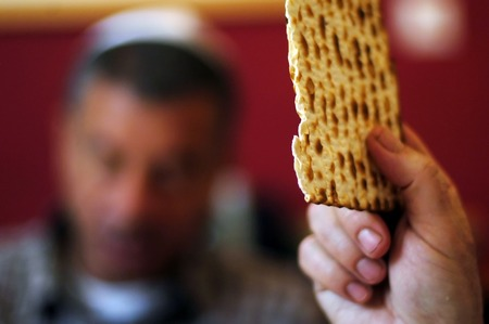 matzah: A man is blessing on Matzah (unleavened bread) while another wearing a kippah (scullcap) reads the Haggadah (traditional text) during blessings for the Jewish holiday of Passover Dinner