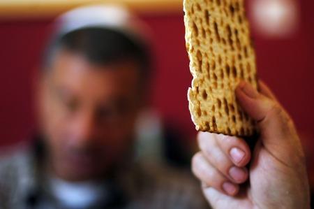 Un homme est une bénédiction sur Matsa (pain azyme), tandis qu'un autre portant une kippa (scullcap) lit la Haggadah (texte traditionnel) pendant des bénédictions pour la fête juive de la Pâque Dîner