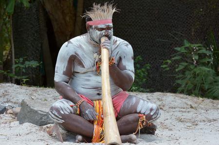 Portrait of one Yugambeh Aboriginal man play Aboriginal  music on didgeridoo, instrument during Aboriginal culture show in Queensland, Australia.