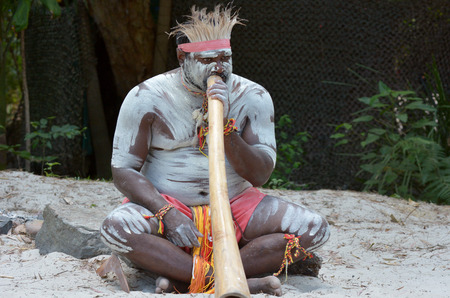Portrait of one Yugambeh Aboriginal man play Aboriginal  music on didgeridoo, instrument during Aboriginal culture show in Queensland, Australia.