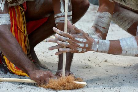 Yugambeh 先住民の戦士の男性の手は、クイーンズランド州、オーストラリアのアボリジニ文化ショーの間に工芸品を作る火災をデモンストレーション 写真素材