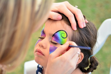 kid portrait: little girl getting her face painted like a butterfly. Stock Photo