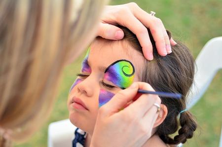 meisje krijgt haar gezicht geschilderd als een vlinder. Stockfoto