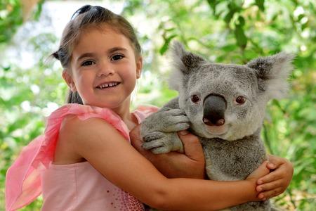 gold coast: Little girl (age 05) hugs Koala in Queensland, Australia.