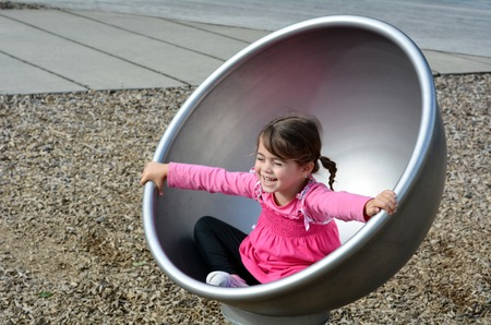 playhouse: Little girl spinning on a  modern merry go round carousel at children toy playground in a park. Stock Photo