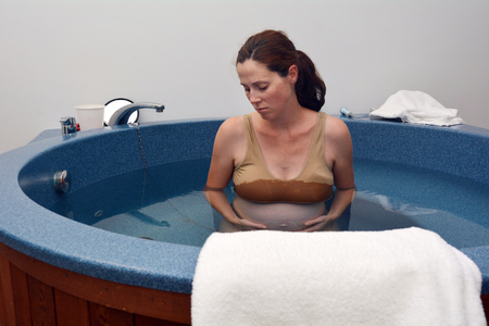 midwifery: Pregnant woman during natural water birth. Stock Photo