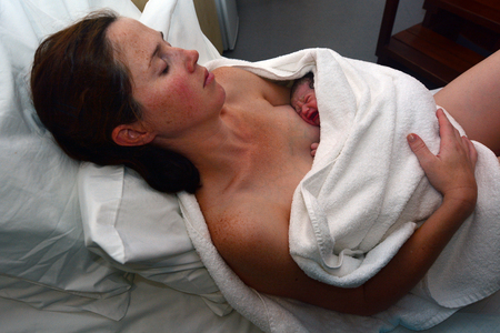 sala parto: Madre di riposo con il suo neonato a letto subito dopo un travaglio parto in acqua naturale. Foto di concetto di donna incinta, neonato, bambino, la gravidanza.