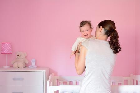 Jonge moeder zet haar baby (meisje leeftijd 06 maanden) te slapen terwijl ze huilt. Concept foto ouderschap en het moederschap.