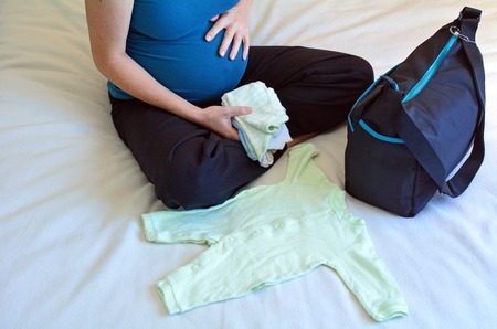 maternity: Pregnancy - pregnant woman packing a Hospital Bag. Concept photo of pregnant women life style and health care. copy space Stock Photo