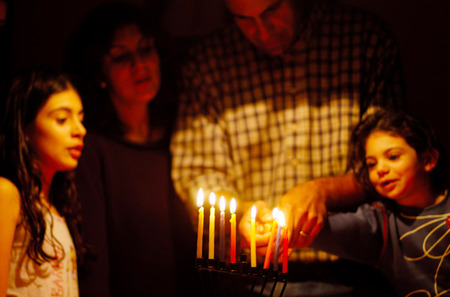 holiday lighting: A family is lighting a candle for the Jewish holiday of Hanukkah. Stock Photo