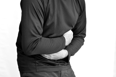 constipation symptom: Man with stomach pain standing against white background. Torso and hands. Concept photo of healthcare and Medical (BW)
