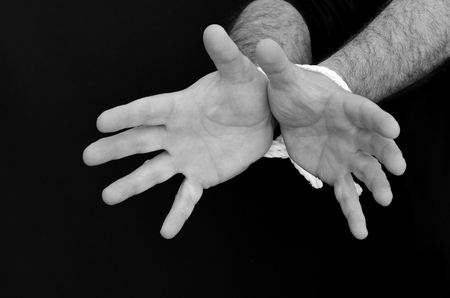 slave labor: Hands of a missing kidnapped, abused, hostage, victim man  tied up with rope in emotional stress and pain, afraid, restricted, trapped, call for help, struggle, terrified, locked in a cage cell. Stock Photo