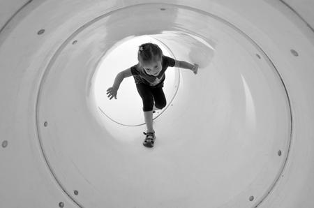 jardin de infantes: Ni�o (ni�a 05 a�os) juega en el t�nel del patio. Ni�ez foto. espacio de la copia (BW)
