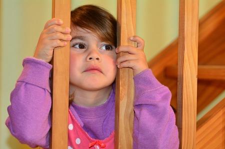 悲しい少女は、ここで就寝前に、家で両親の戦いに見えます。子供、子供の頃、家族、問題、離婚、虐待、暴力の概念写真。