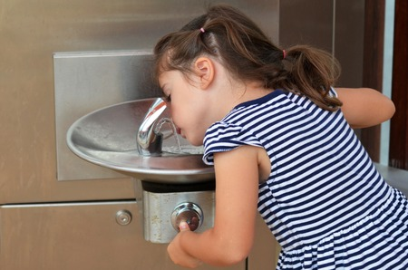 Little girl (age 04) drink water from  outdoor water fountain. Stock Photo