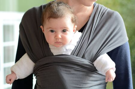 wraps: bebé recién nacido llevado por su madre con una envoltura de bandolera. Foto del concepto del bebé recién nacido, madre, maternidad, cuidado de la salud, el transporte, el transporte.