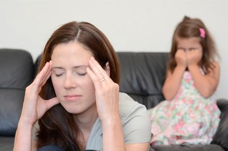 agotado: Madre deprimida joven (30 años) con su hija llorando en el fondo. Foto de archivo