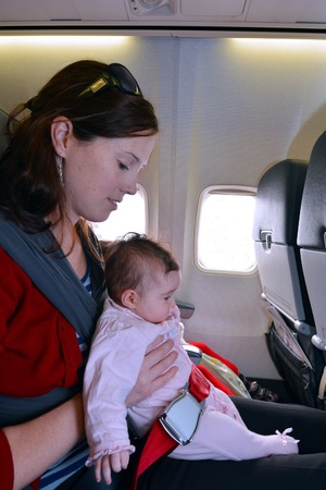 air baby: Mother carry her infant baby during flight.Concept photo of air travel with baby.