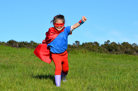 pretend: Superhero child girl runs against dramatic blue sky outdoor background with copy space. concept photo of Super hero, girl power, play pretend, childhood, imagination.