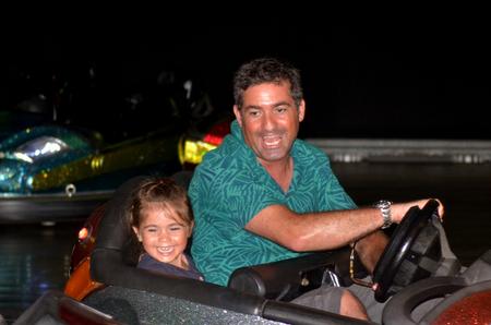 parish: Father and child ( girl age 04) having fun driving  a bumper car.