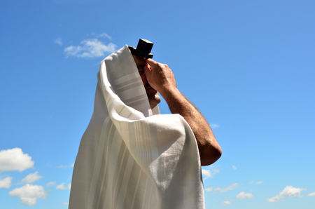 An Jewish orthodox man prays with a blue sky background, reads a torah book (siddur) and wears, tefillin, tzitzit and tallit. Banque d'images