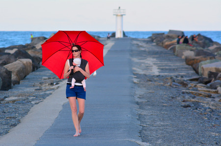 seaway: Young mother carry her infant baby and red umbrella in Seaway Gold Coast Australia. Stock Photo