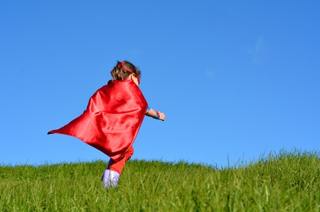 pretend: Superhero child girl  runs in a green field against dramatic blue sky background with copy space. concept photo of Super hero, girl power, play pretend, childhood, imagination.