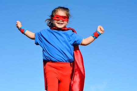 pretend: Happy Superhero child (girl) against dramatic blue sky background with copy space. concept photo of Super hero, girl power, play pretend, childhood, imagination.