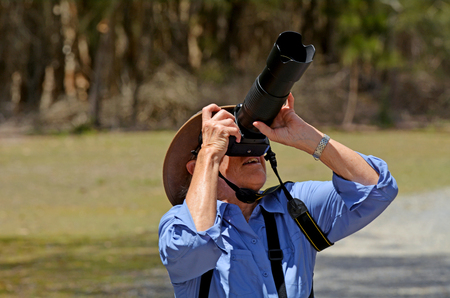 gold coast australia: Mature woman with camera photographing wildlife in Coombabah Lake Conservation Park IN Gold Coast, Australia