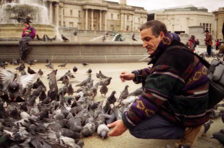 trafalgar: Tourist feeds pigeons in Trafalgar Square.
