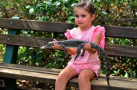 indopacific: Brave child ( girl age 05) holds a young baby Australian Salt water crocodile.