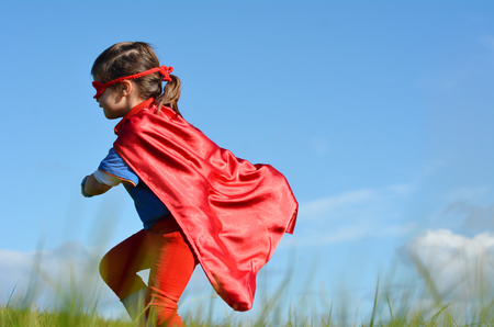 pretend: Superhero child (girl)  runs in a green field against dramatic blue sky background with copy space. concept photo of Super hero, girl power, play pretend, childhood, imagination.